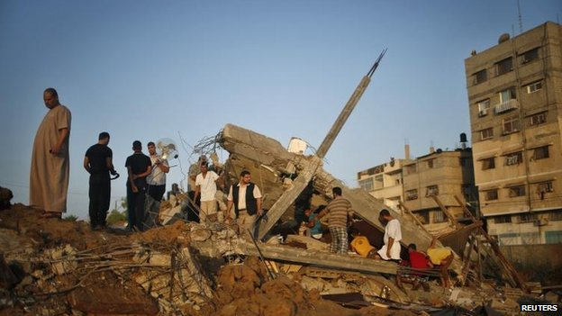 Palestinians in Gaza City survey the rubble of a house targeted in an Israeli air strike, 9 July