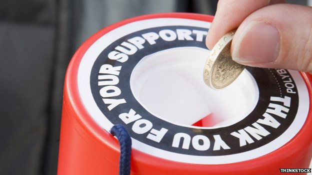 Somebody putting a pound into a charity collection tin