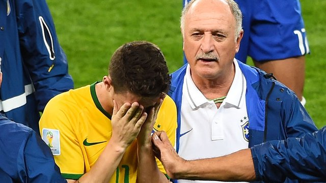Scolari consoles midfielder Oscar on the final whistle