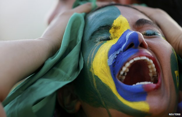 A Brazil fan holds her head in despair during the semi-final defeat to Germany