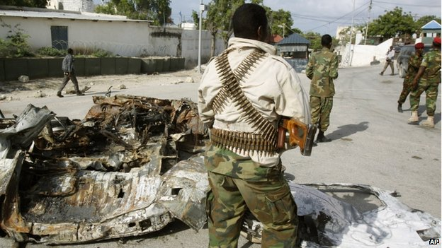 Somali soldiers stand near the wreckage of a car bomb that was detonated at the main gate of the presidential palace in Mogadishu, Somalia, Wednesday, 9 July 2014