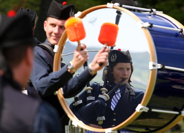 A female member of the pipe band of Corby is reflected in a drum as she plays the bagpipes