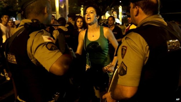 A female Brazilian supporter shouts insults at the police