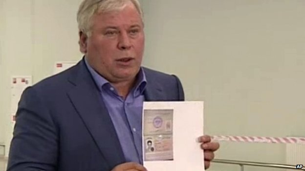 Russian lawyer Anatoly Kucherena shows a temporary document that allowed Edward Snowden the right to cross the border into Russia (1 August 2013)
