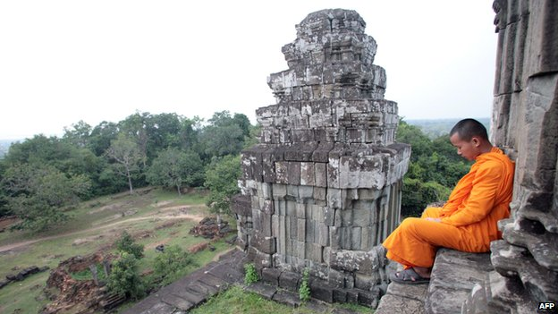 Monk sits on stairs at the Bayon Temple in Angkor, Cambodia