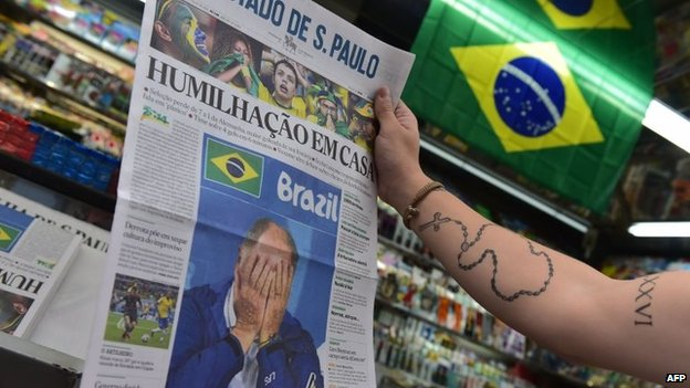 A passer-by looks at the front page of a newspaper on display at a news stand in Sao Paulo on 9 July, 2014.