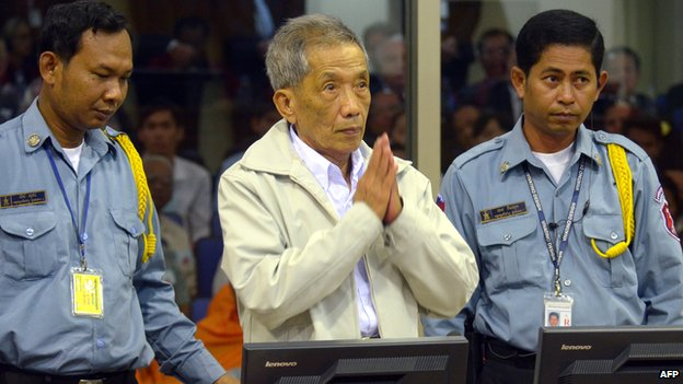 Fomer Khmer Rouge prison chief Kaing Guek Eav - better known as Duch (c) - greets judges at Cambodia's UN-backed war crimes court in Phnom Penh on February 2012.