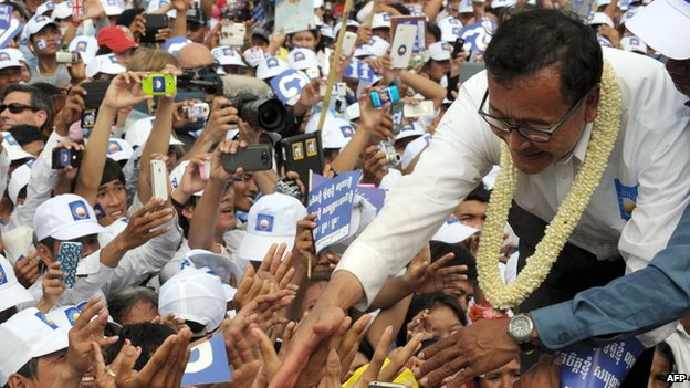 Sam Rainsy, the leader of opposition Cambodia National Rescue Party (CNRP), shakes hands with supporters at Democracy Park during the general election campaign in Phnom Penh on 26 July 2013.