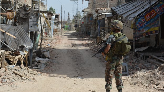Soldier stands on empty road lined with destroyed buildings in Miranshah
