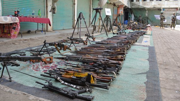 Dozens of guns laid in a line in Miranshah