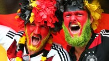 Two Germany fans wearing face paint celebrate victory against Brazil