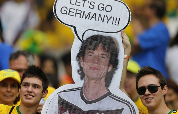 Brazil supporters hold a poster depicting Rolling Stones singer Mick Jagger wearing a Germany shirt prior to the World Cup semi-final