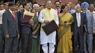 India's Finance Minister Arun Jaitley (C) poses as he leaves his office to present the federal budget for the 2014/15 fiscal year, in Delhi July 10, 2014