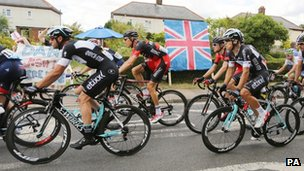 The Peloton passes a Union flag as the Tour de France passes through Bannister Green near Felsted in Essex