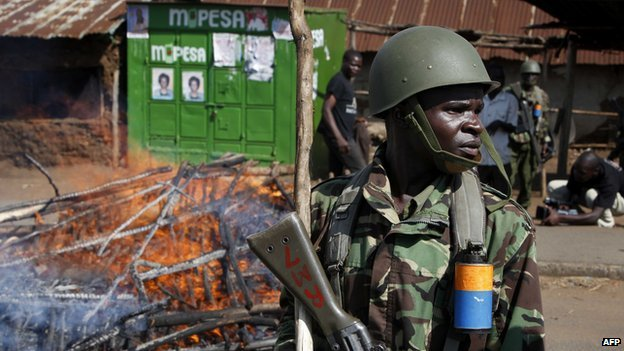 A Kenyan police officer stands near a burning road block which was set up by an angry mob at Nyalenda slum in Kisumu after the official declaration of the final results of the presidential elections on 9 March 2013