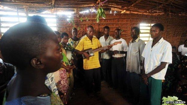 Un homme joue de la guitare faite de bois et une boîte vide d'huile tout en menant d'autres dans la chanson lors d'un service de prière dans une église de Mutambara, Burundi - 2010