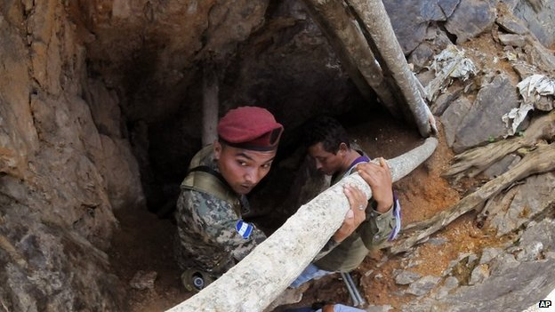 A soldier stands guard at the entrance of a collapsed gold mine where miners are trapped in San Juan Arriba, on 4 July, 2014.
