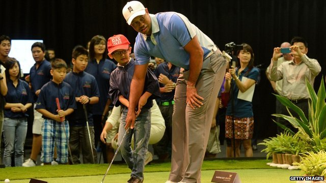 Tiger Woods helps an Asian child with their putt