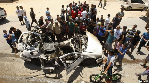 Palestinians gather around the remains of a car which police said was targeted in an Israeli air strike in the northern Gaza Strip on 10 July 2014.
