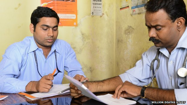 Two men sitting reading papers, one with stethoscope round his neck