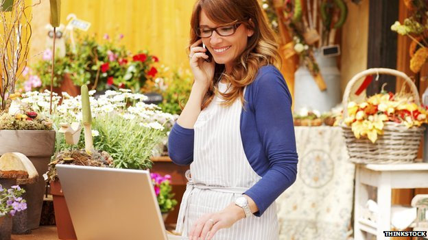 Woman in a flower shop with laptop