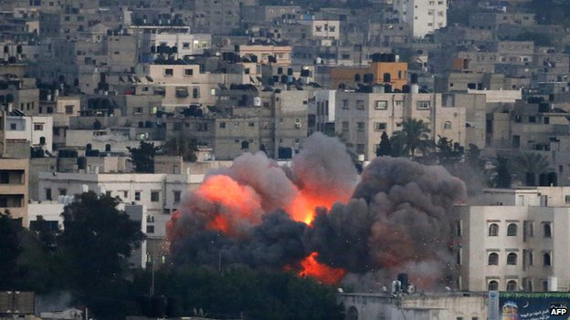 Flames erupt from a building hit by an Israeli air strike on 9 July 2014 in Gaza City.