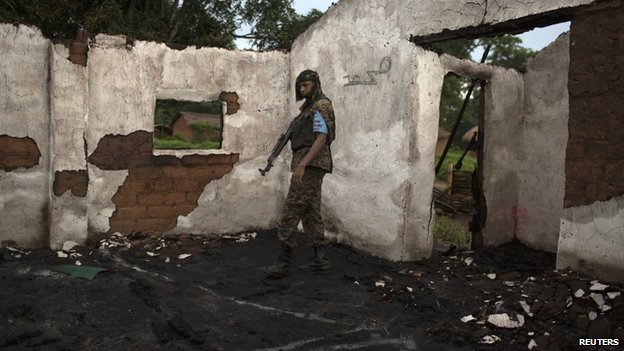 A Seleka soldier stands in the ruins of a mosque, which residents say was attacked and burnt by anti-balaka militiamen