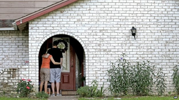 A family who identified themselves as friends of the victims, pauses on the porch after placing flowers and a framed photograph at the door of the home where a gunman killed six people Wednesday in Spring, Texas 10 July 2014