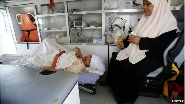 Palestinian woman, who medics said was wounded in an Israeli air strike, lies on a bed inside an ambulance waiting to cross into Egypt, at Rafah crossing in southern Gaza Strip