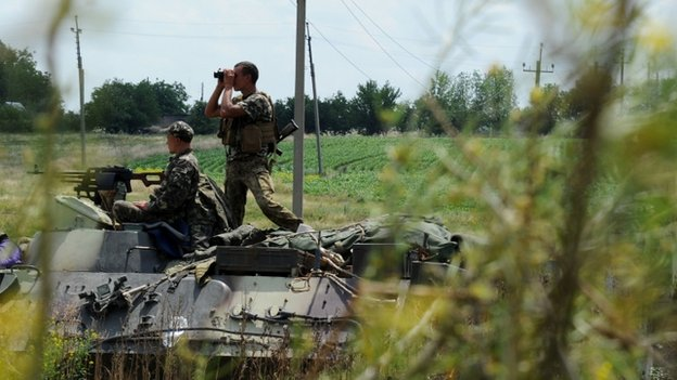 A Ukrainian government soldier looks though binoculars from the top of an armoured vehicle as Ukrainian troops take up a position some 20km south of Donetsk, eastern Ukraine on 10 July 2014