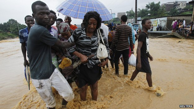 People walking though floods