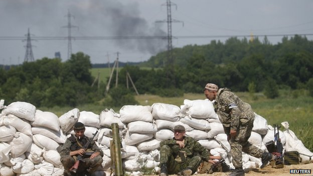 Pro-Russian separatist fighters from the so-called Battalion Vostok (East) wait behind a sandbag wall at a checkpoint on the outskirts of Donetsk on 10 July 2014