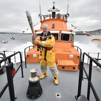 Graham Campbell carries the Glasgow 2014 Queen's Baton on an RNLI lifeboat from Hatston Harbour to Kirkwall Harbour
