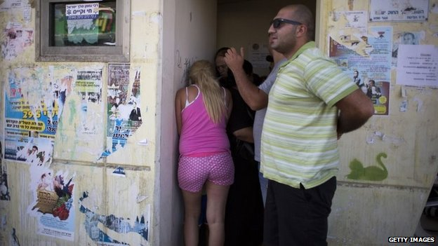 "People seen in shock during a ""colour red"" siren on July 10, 2014 in Sderot, Israel."