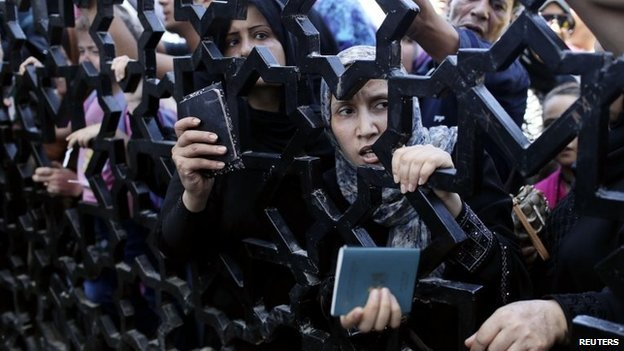 Palestinians hold their passports as they try to cross into Egypt