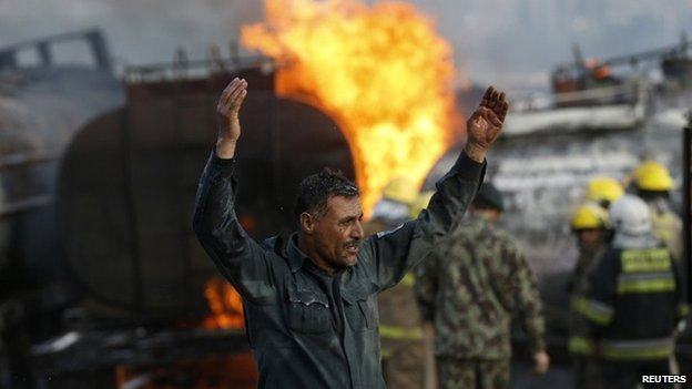 A policeman reacts at the site of burning fuel trucks after a overnight attack by the Taliban on the outskirt of Kabul July 5, 2014.