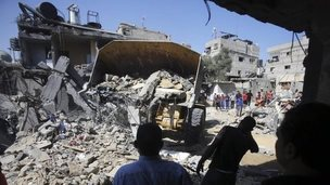 People look at a house which Palestinian officials say was destroyed in an Israeli air strike in Khan Younis. Photo: 10 July 201