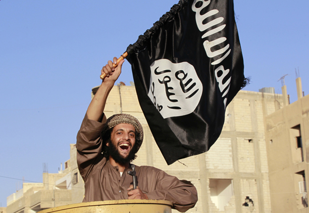 A jihadi flying the black flag of Islam in the city of Raqqa, Syria