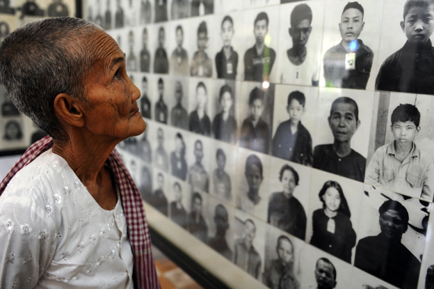 A Cambodian grandma looks at portrait photos of victims of the Khmer Rouge at the Tuol Sleng genocide museum in Phnom Pen
