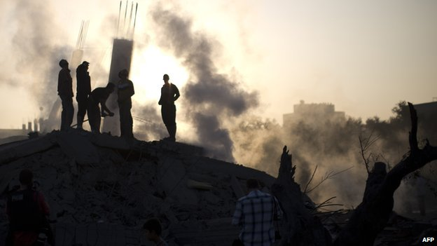 Palestinian men inspect the site of an Israeli military strike in Gaza City on 8 July 2014 .