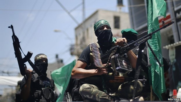 Palestinian members of Hamas armed wing take part in the funeral of their comrades in Gaza City on 21 June 2014