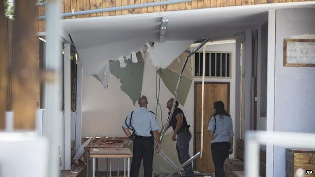 Israeli police check damage from a rocket on a synagogue in Tel Aviv, 11 July