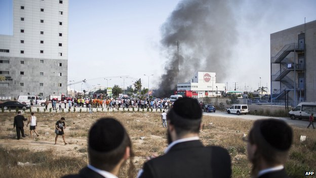 People watch as fire-fighters try to douse a fire from a rocket that hit a Petrol station on 11 July 2014 in Ashdod, Israel.