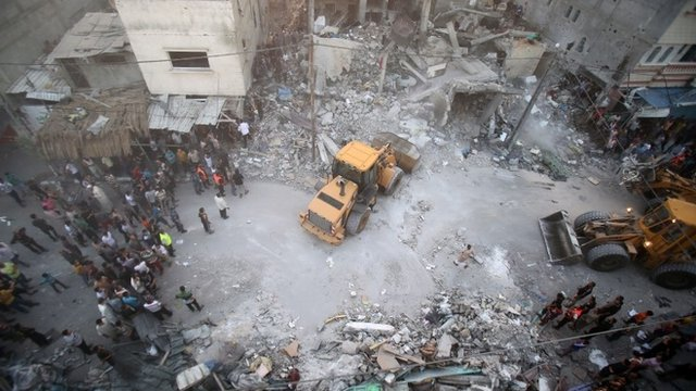 A digger removes the rubble of the Ghanam family home after it was targeted in an Israeli air raid on Rafah, in the southern of Gaza strip, on July 11, 2014