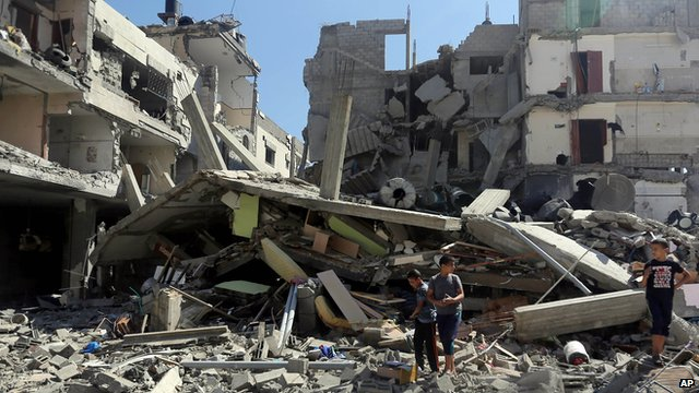 Palestinians inspect the rubble of a building in Gaza city that was hit by Israeli rocket fire