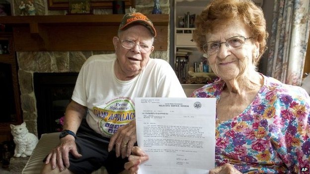 Harold Weaver sits behind his wife, Martha, in their Nickleville, Pennsylvania  home. Martha holds a letter from the Selective Service for her late father, Fred Minnick, requiring him to register for the nation's military draft 8 July 2014