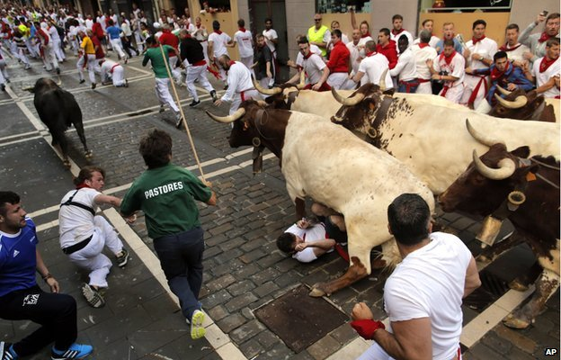 A bull running over Tom Hadfield in Pamplona, Spain, on 8 July 2014