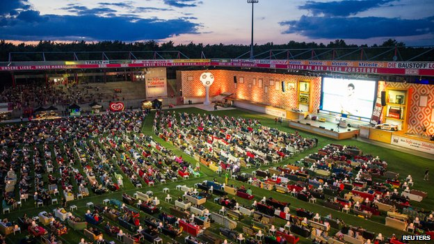 People sit on sofas as they watch the opening game of the 2014 World Cup between Brazil and Croatia, during a public viewing event at the Alte Foersterei stadium in Berlin on 12 June 2014