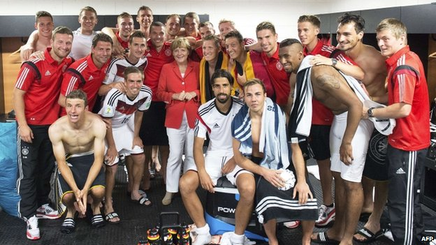 German Chancellor Angela Merkel (C) poses with the German squad after they beat Portugal on 16 June 2014.