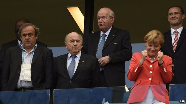 German Chancellor Angela Merkel (R) gestures next to FIFA President Sepp Blatter (C) and UEFA President Michel Platini (L) prior to the Germany-Portugal match in Salvador on 16 June 2014.